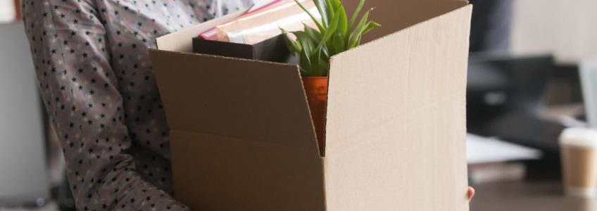 Woman Carrying Box of Belongings out of Office after Losing Job